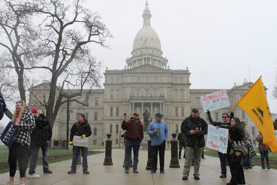 Protesters gather in front of the Michigan Capitol on Wednesday, April 15, 2020, to protest Gov. Gretchen Whitmer's stay-at-home order. People are supposed to remain six feet apart to stem the spread of the virus.