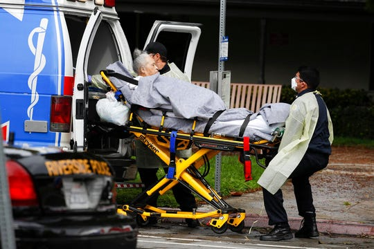 This April 8, 2020, file photo shows a patient being evacuated from the Magnolia Rehabilitation and Nursing Center in Riverside, Calif.