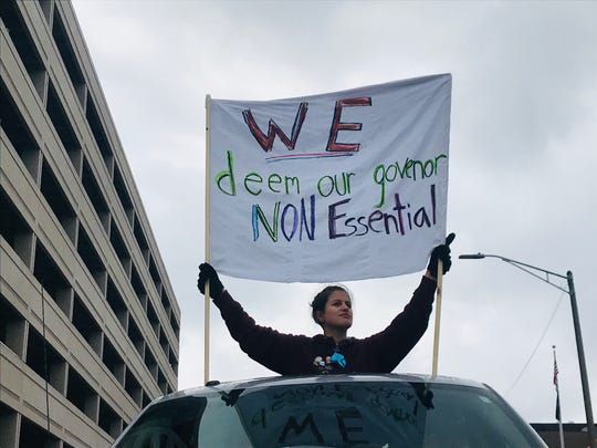 An unnamed protester holds a sign against Gov. Gretchen Whitmer during a demonstration on Wednesday, April 15, 2020. Hundreds of protesters gathered at the Capitol to voice their frustration with Whitmer's stay-at-home order.
