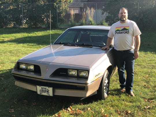 Beltz poses with his 1983 Pontiac J2000, one of the most unexpected cars in his collection.