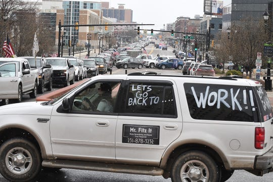 """People in vehicles protest the Governor's stay home order during """"Operation Gridlock"""" in Lansing Wedesday."""