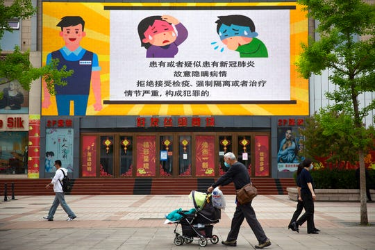 People wear face masks to protect against the spread of the new coronavirus as they walk past a screen showing a video about criminal penalties for not cooperating with medical rules in Beijing, Wednesday, April 15, 2020.