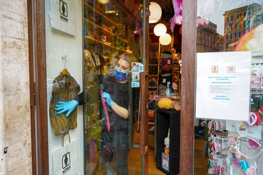 Camilla Cocchi wears a face mask and gloves as she sorts out clothing in her children's clothes shop after it was allowed to reopen following lockdown measures to contain the spread of Covid-19, in Rome, Tuesday, April 14, 2020.