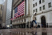 In this March 19, 2020, file photo, a pedestrian wearing a surgical mask and gloves walks past the New York Stock Exchange in New York.