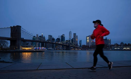 A jogger wearing a mask runs along Brooklyn Bridge Park, Tuesday night, April 14, 2020 during the coronavirus pandemic in New York.