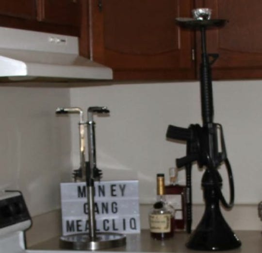 The Money Gang Meal Clique sign and assault-rifle ashtray found in the Baltimore apartment.