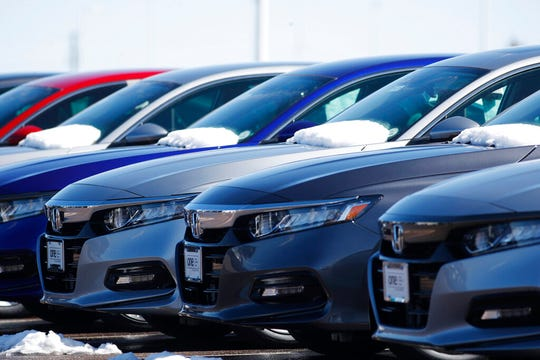 In this Sunday, March 22, 2020, photograph, a row of unsold 2020 Accord sedans sits at a Honda dealership in Highlands Ranch, Colo.