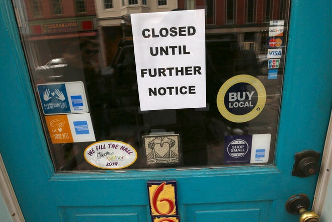 In this March 25, 2020 file photo,  a closed sign hangs in the window of a shop in Portsmouth, N.H., due to caronavirus concerns.