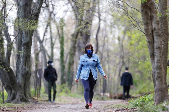 Alfina Schicker takes a solitary walk through the woods in Brooklyn's Prospect Park, Tuesday, April 14, 2020 during the coronavirus pandemic in New York.