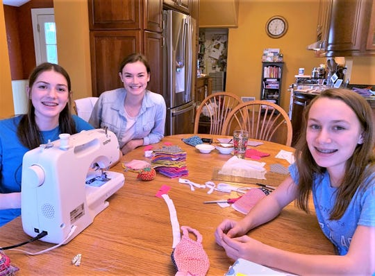 Corning Painted-Post High School senior Angelea Collins, back, with help from her sisters Victoria, left, and Cassandra Collins, is making and collecting hundreds of face masks to help local organizations respond to COVID-19.