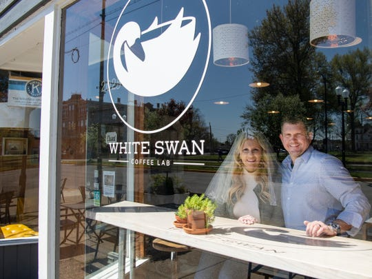 Charles and Carrie Sidwell pose in the spot of their first date, White Swan Coffee Lab, in Evansville, Ind., Friday afternoon, April 10, 2020. The couple pushed their wedding date up, but still had to follow the new coronavirus rules only allowing up to 10 people to be present at their wedding... including them. Their parents, pastor and a wedding photographer were present.