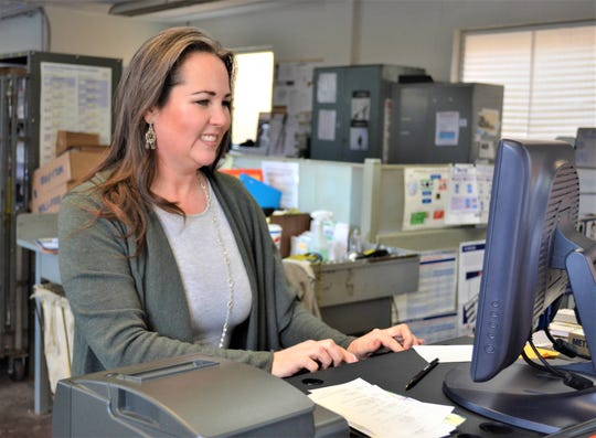 Woodville postmaster Sarah Susor works at the post office on March 23. In her spare time, she writes books about her family's adventures with her seven-year-old daughter, Savannah.