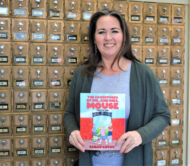 """Woodville postmaster Sarah Susor holds her first book, """"The Adventures of Mr. and Mrs. Mouse: Trip to the Zoo,"""" inside the Woodville Post Office."""