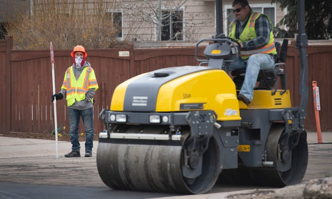 A city worker wears a bandana while he directs traffic as the crew works to resurface the road along Ticonderoga Drive in Fort Collins, Colo. on Wednesday, April 15, 2020. While many city and county employees are working from home, Fort Collins road crews are still working in the field during the coronavirus pandemic.