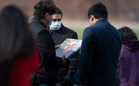 Mourners hold a photo of Saul Sanchez, a longtime JBS employee that died of the coronavirus disease, during his funeral at Sunset Memorial Cemetery in Greeley, Colo. on Wednesday, April 15, 2020.