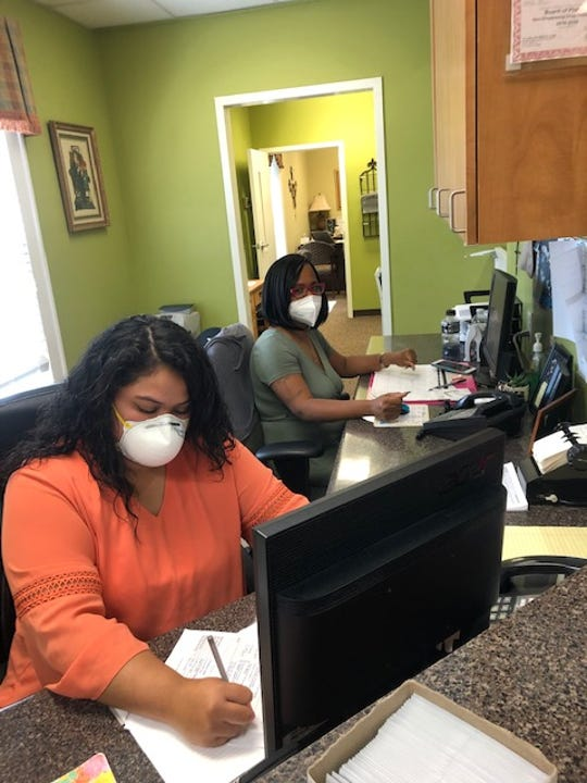 Patient Services Coordinator Clarissa Clark and receptionist Michele Cifuentes wear face masks to check in patients at the Taylors Free Medical Clinic.