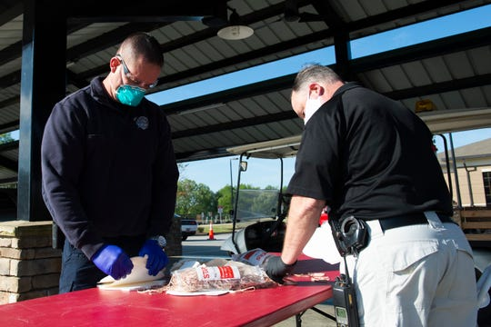 Travelers Rest Police and Fire Departments hand out paper masks in Trailblazer Park in Travelers Rest Wednesday, April 15, 2020. The masks were made and donated by Paper Cutters, Inc.