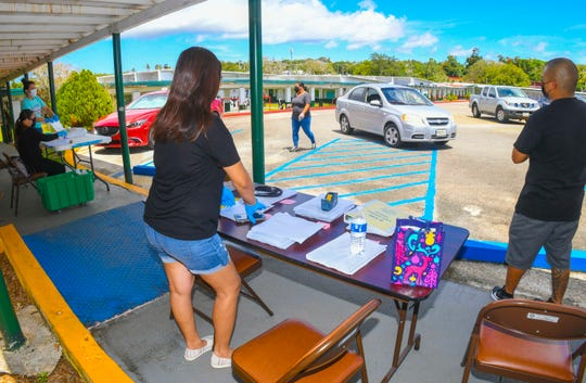 Parents pick up distant learning lesson packets for their children, who would normally be attending Daniel L. Perez Elementary School in Yigo, on Thursday, April 15, 2020. The material, being distributed as part of the Guam Department of Education's Grab & Learn program at the campus and 25 other public elementary schools, contain lessons and activities in literacy, math and character education/life skills for students and families who do not have reliable or consistent internet access, according to GDOE.