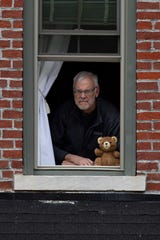 """Greg Pritchett peers from his second-floor downtown Henderson window Wednesday afternoon. There's a teddy bear placed on the sill for kids to spot while on """"bear hunts"""" to pass the time during the coronavirus lockdown. Pritchett was diagnosed with COVID-19 and hospitalized at Ascension St. Vincent in Evansville. He is now recovering."""