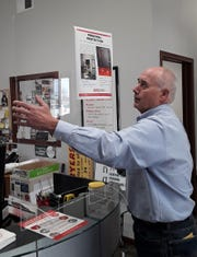 "Dennis Tallman adjusts the clear acrylic shield used to protect staff and customers at the AlphaGraphics reception counter in his North Liberty printing business. The ""personal protection"" poster at the top is attached to the shield, which is so clear it is hard to see."