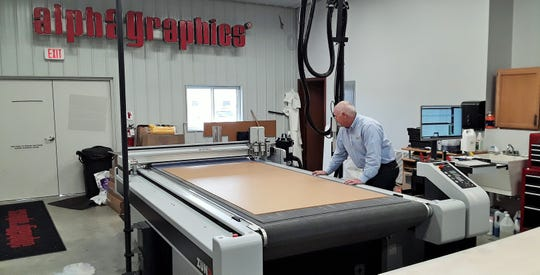 This high-tech CNC router cuts precise shapes from large acrylic sheets using designs fed into its computer. Normally used to create signs, it is now also used by AlphaGraphics to build protective table or countertop shields needed during the pandemic.