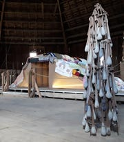 """Two more sculptures by Jennifer Vess are shown in the enormous loft area of the historic octagonal barn. Behind the work at right titled """"All the burdens I cannot carry"""" is the exhibit's most prominent piece titled """"Fortress."""" The tent-like structure is covered with 110 blankets and quilts loaned and donated for the sculpture from friends and relatives throughout the U.S."""