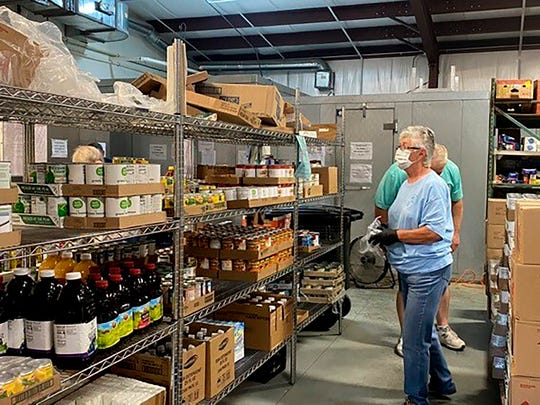 Volunteer Sandra Robert looks over items donated to the Hancock County Food Pantry to prepare boxes of food for families on Tuesday, April 14, 2020, in Hancock County, Miss.