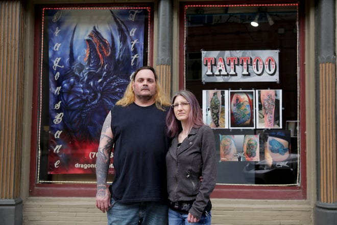 Sean and Carrie McGill, owners of DragonsBane Tattoo, stand outside their closed Columbia Street store amid the Coronavirus pandemic, Wednesday, April 15, 2020 in Lafayette.