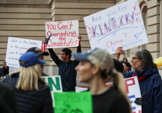Protestors yell 'Open Up Kentucky' and 'You're not a king. We won't kiss your ring' outside the the state capitol Wednesday in Frankfort where Gov. Andy Beshear was giving his daily Coronavirus updates. More than hundred people protested. April 15, 2020