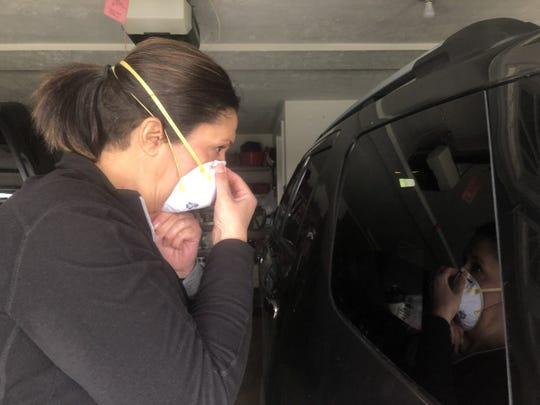Jenny Eyre, a home health care case manager and registered nurse with Sparrow Home Care, demonstrates using the reflection she sees on the outside of her vehicle window to make sure N95 mask she wears are on properly. During a given work day her vehicle serves as her mobile office. It's organized with medical supplies, forms and protective equipment.