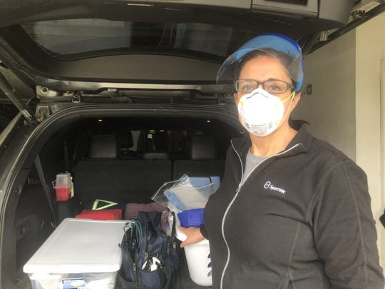 Jenny Eyre, a home health care case manager and registered nurse with Sparrow Home Care,  at her home in Laingsburg before leaving to see patients in their homes. She works out of her vehicle, which is filled with supplies and equipment.