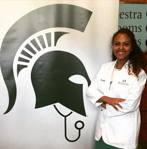 Sophia Tessema, a fourth-year student at the Michigan State University College of Human Medicine, helped develop an online questionnaire that tells people if they're likely infected with COVID-19. She is shown posing in front of a Michigan State University logo.