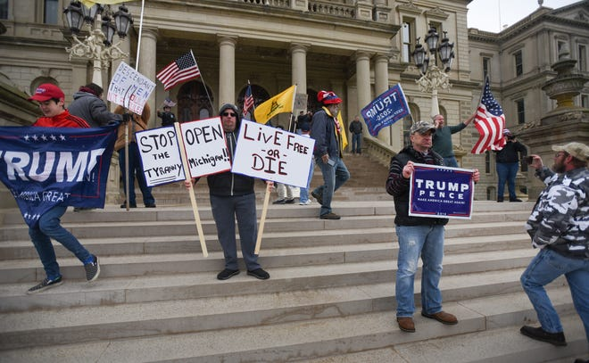 Rallygoers protest against Michigan Gov. Gretchen Whitmer's stay-at-home order Wednesday, April 15, 2020, in downtown Lansing, Mich. at the State Capitol.