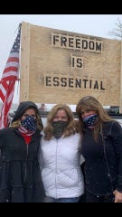 From left, Molly Hiotaky-Watts, Ellen Ernst and Kathy Rahmanian Trask pose for a photo as crowds arrive in Lansing to protest Gov. Whitmer's stay at home order on Wednesday, April 15, 2020.