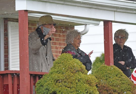 Fred Williams and his wife LulaMae wave to well-wishers Wednesday afternoon from their porch as a caravan of friends and family drove by the house and honked to celebrate Fred turning 100 years old.