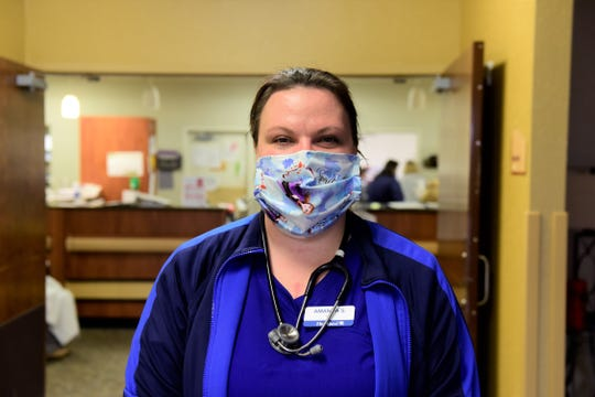 Amanda Shulaw, LPN, shows off her mask inside Heartland of Bucyrus. Every staff member at the facility wears a mask to help prevent the spread of the novel coronavirus that causes COVID-19.