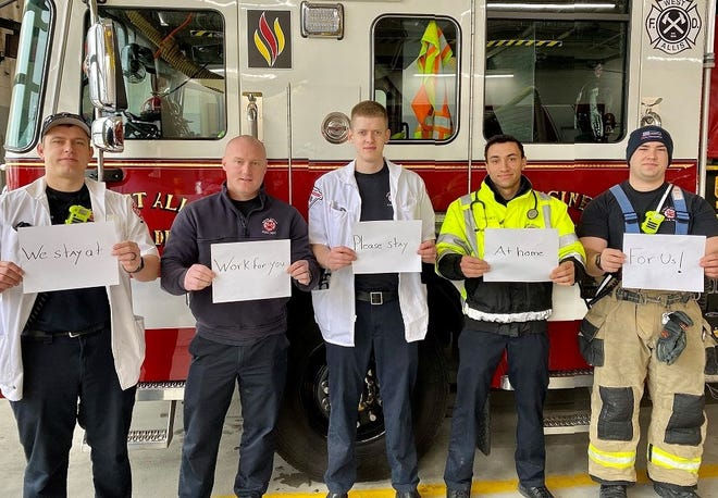 """Members of the West Allis Fire Department (from left) Lt. Patrick Schrader and firefighters Dan Groh, Andrew Crum, Kade DeLacy and Lucas Houk display signs that say, """"We stay at work for you, please stay at home for us."""" The department recently suspended accepting homemade and store-bought food from community members due to COVID-19."""