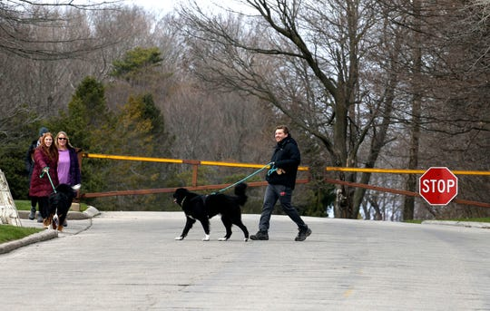 Neighbors enjoy the outdoors as they walk their dogs along the closed Grant Park parkway on April 15. The park is open, but the parkway has been closed due to the coronavirus. The Wisconsin Bike Fed is calling on cities to close more streets to cars so people can use them for walking and biking.