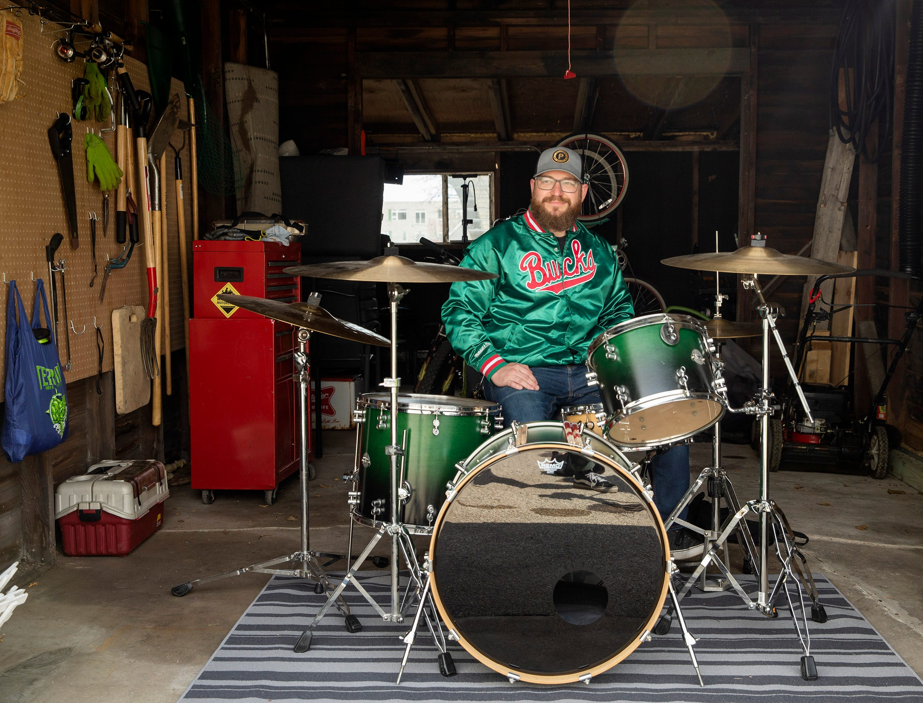 Kyle Ciske sits in front of his drum set in his garage in West Allis. Ciske was the head brewer for The Explorium Brewpub but was laid off nearly four weeks ago. Ciske has started filling the days with activities he once neglected.