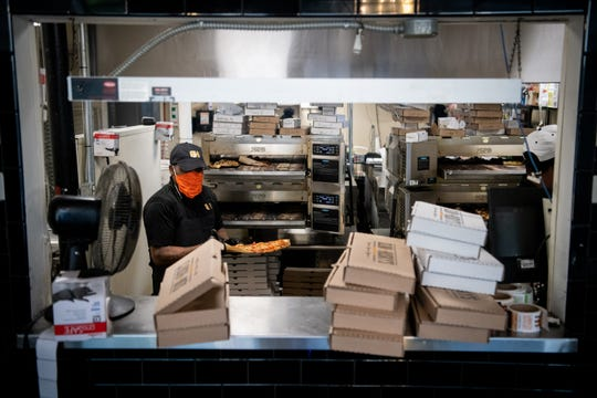 Pizzas are prepared in the kitchen at Slim & Husky's The Rollout in Nashville, Tenn., Tuesday, April 14, 2020.
