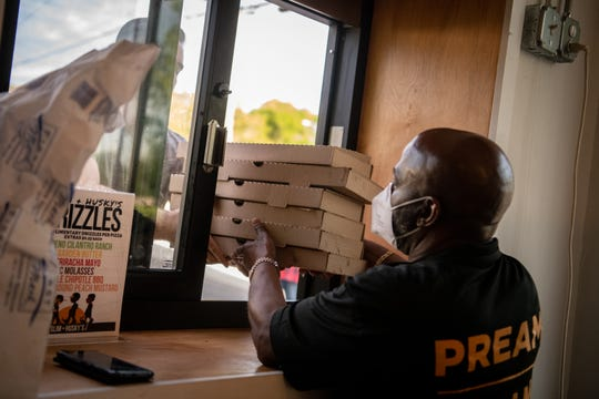 Antonio Ervin hands an order to a customer through the takeout window at Slim & Husky's The Rollout in Nashville, Tenn., Tuesday, April 14, 2020.