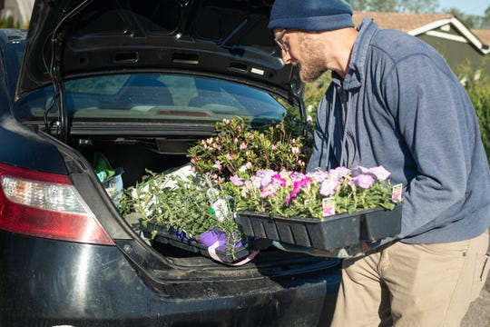 Bates employee Justin Morris loads flowers for a customer's curbside pickup at Bates Nursery and Garden Center.