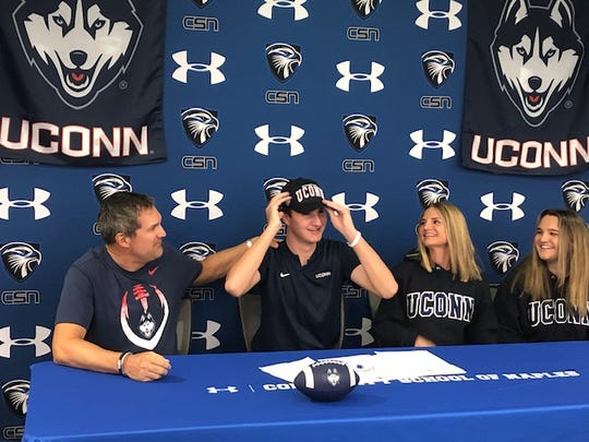 Community School of Naples punter Blake Otto puts on a University of Connecticut hat after signing to play football for the Huskies on Wednesday, April 15, 2020. Otto is joined by (from left) his dad, Keith, his mom, Danielle, and his sister, Dominique.