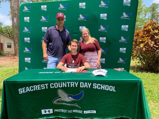 Seacrest soccer player Christian Fischer signs a letter of intent to play at Bellarmine, a Division I school in Kentucky, at his house on Wednesday, April 15, 2020. Fischer's parents, Patrick and Louanne, are behind him.