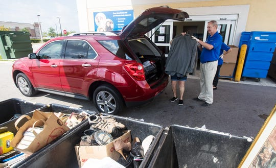 Mark Carpenter an employee of the Goodwill Store at Heritage Bay in North Naples takes an item from a client on Wednesday, April 15, 2020.