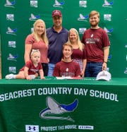 Seacrest soccer player Christian Fischer, surrounded by his family, signs a letter of intent to play at Bellarmine, a Division I school in Kentucky, at his house on Wednesday, April 15, 2020.
