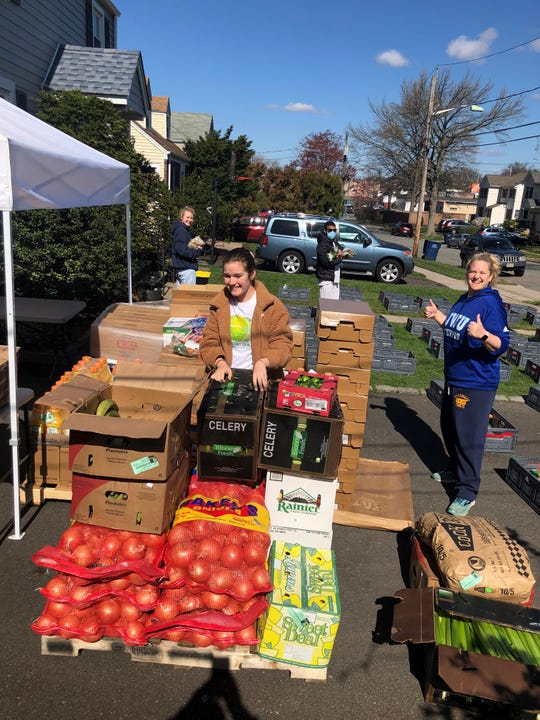 Cori Carroll, at right, puts together grocery bags of fresh food to be donated to needy families who have been affected financially by the COVID-19 crisis. Her daughter, Mackenzie Carroll, helps.