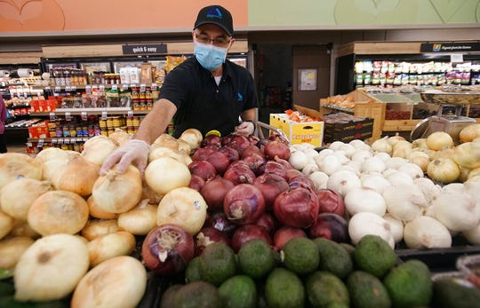 Albertsons Grocery store Produce Manager Jake Sandoval stocks onions at the store located in the South Valley of Albuquerque on Wednesday April 8, 2020. New Mexico governor MIchelle Lujan Grisham and state health officials briefed the public on Wednesday, April 15, saying social distancing is helping to slow the spread of the COVID-19 coronavirus.