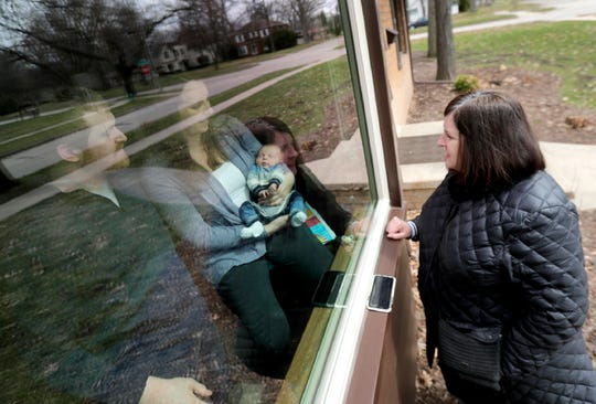 Ryan and Cortney Dvorachek of Appleton hold their newborn son Emmett in the front window of their home during a visit with the baby's grandmother Sheree Joosten of Menasha. The conornavirus pandemic has put in-person interaction on hold.