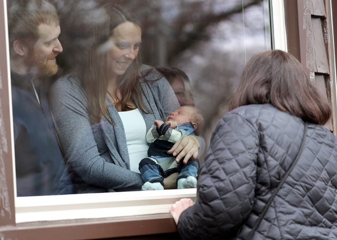Ryan and Cortney Dvorachek, along with their newborn son Emmett, visit with the baby's grandmother, Sheree Joosten, through the front window of their Appleton home on Wednesday.